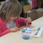 Girl painting a butterfly art project