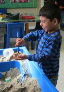 Boy playing with sand at the sensory table