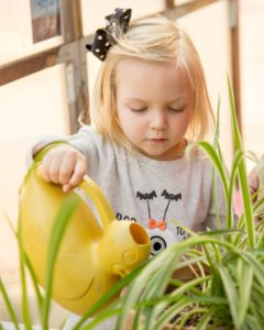 Girl watering a plant in the greenhouse