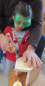 Girl hammering a birdhouse